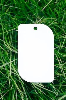 Widok z góry na pojedynczą białą metkę z ceną na odzież w kształcie liścia kreatywny układ trawnika zielonej trawy z metką na logo.