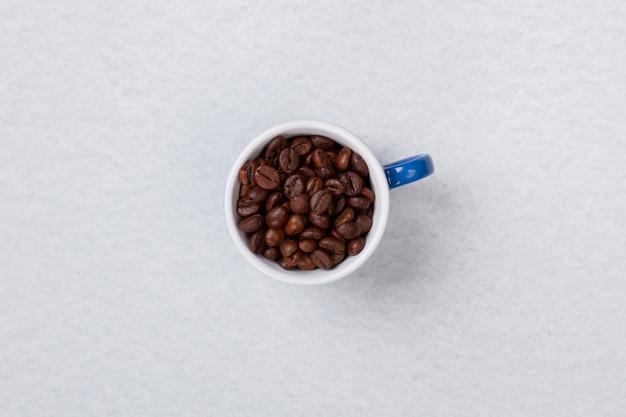 Widok z góry na pojedynczą filiżankę wypełnioną ziarnami kawy