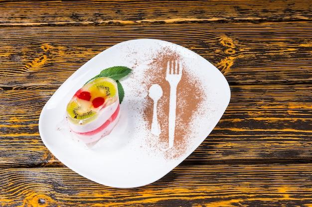 Widok z góry na pojedynczy deser owocowy zwieńczony kiwi i wiśniami - ułożony tak, aby przypominał buźkę - przyozdobiony miętą i podany na białym talerzu z posypką kakao