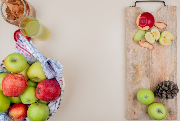 Widok z góry na pokrojone i całe jabłka ze skorupą i szyszką na desce do krojenia z dżemem jabłkowym kosz jabłek i soku jabłkowego na tle kości słoniowej z kopią miejsca