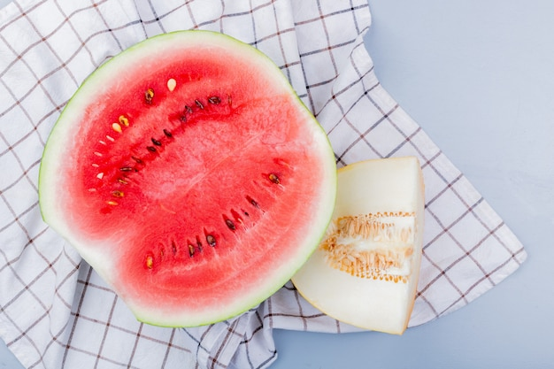 Widok z góry na pokrojone owoce jako arbuz i melon na kraciastej tkaninie i niebieskawo-szarym tle
