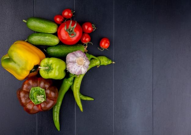 Widok z góry na pokrojone warzywa i całe pomidory, ogórek, czosnek, pieprz na czarnej powierzchni