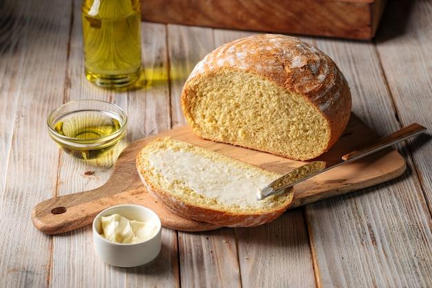 Widok z góry na pokrojony bochenek chleba z oliwą z oliwek posmarowany masłem na drewnianym stole