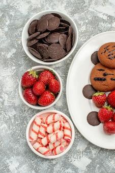 Widok z góry na pół czekoladowe ciasteczka truskawki i okrągłe czekoladki na białym owalnym talerzu i miseczki z cukierkami truskawki czekoladki na szaro-białym podłożu