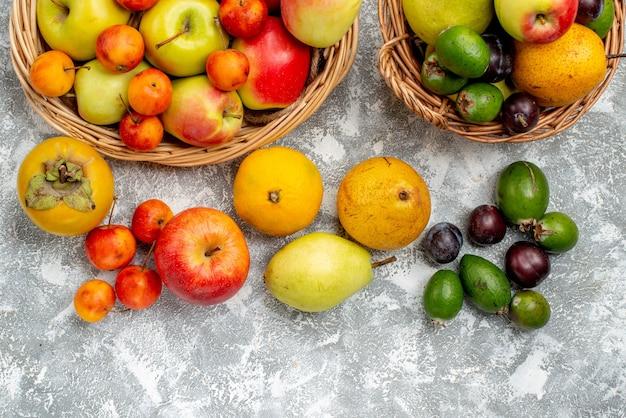 Widok z góry na pół czerwone i żółte jabłka i śliwki feykhoas gruszki i persymony w wiklinowych koszach, a także na ziemi