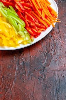 Widok z góry na pół kolorowe papryki cięte na białym talerzu na ciemnoczerwonym stole wolne miejsce
