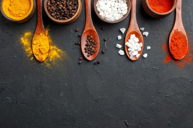 Widok z góry na pół miski poziome rzędy z kurkumą pieprzem czarnym sae sól pieprz czerwony w proszku drewniane łyżki na czarnej powierzchni