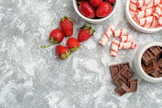 Widok z góry na pół miski z truskawkami, czekoladkami, cukierkami i niektórymi truskawkowymi czekoladkami, po prawej stronie szaro-białej mozaiki