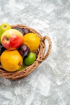 Widok z góry na pół wiklinowy kosz z jabłkami, gruszkami, śliwkami feykhoas i persimmonami po lewej stronie szarego stołu