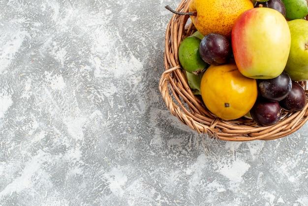 Widok z góry na pół wiklinowy kosz z jabłkami, gruszkami, śliwkami feykhoas i persimmonami w prawym górnym rogu szarego stołu