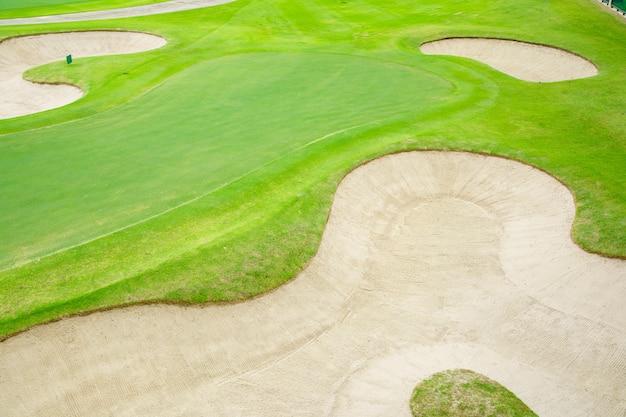 Widok z góry na pole golfowe, piękny piasek bunkrów, kładzenie zielonej i zielonej trawy, fairway rough.