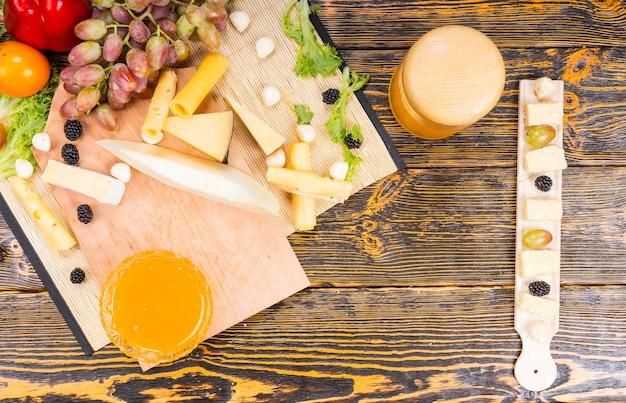 Widok z góry na półmisek serów na bufecie z asortymentem wykwintnych serów, świeżych winogron i miski maczanego miodu na drewnianym stole