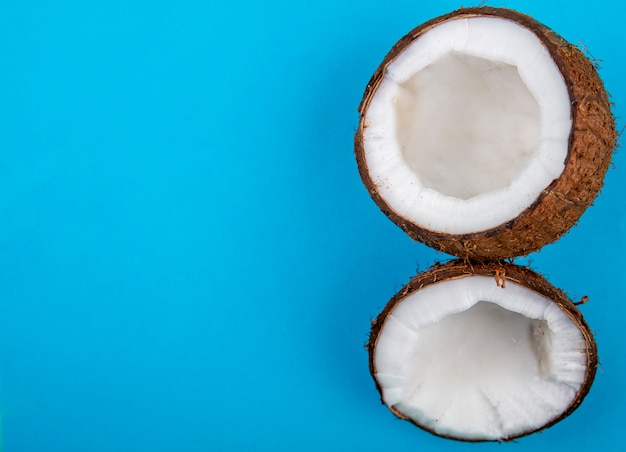 Widok z góry na połowę świeżych dużych kokosów na niebieskiej powierzchni