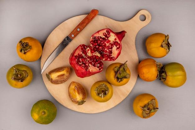 Widok z góry na połówki granatu na drewnianej desce kuchennej z nożem z owocami persimmon i mandarynkami na białym tle