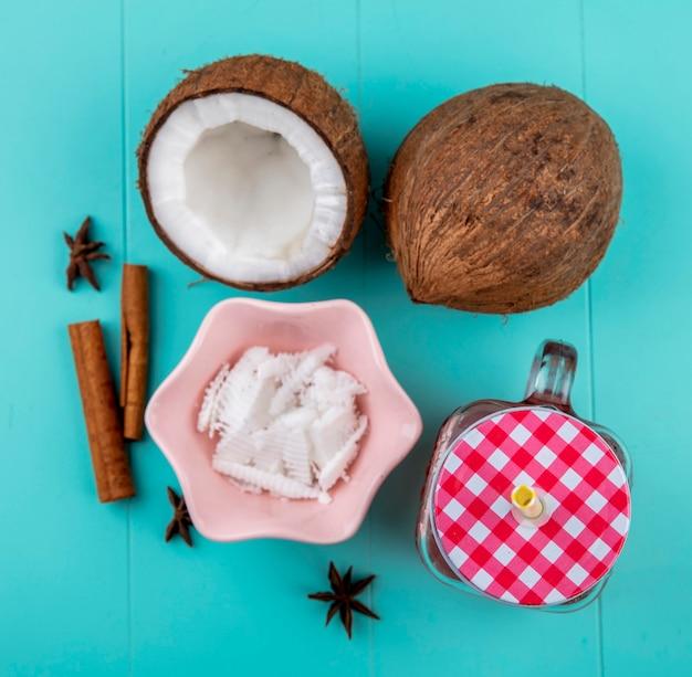 Widok z góry na połówki i całe orzechy kokosowe z miazgą kokosową w różowej misce z sokiem cynamonowym i anyżowym w szklanym słoiku na niebieskiej powierzchni