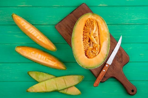 Widok z góry na połówki melona kantalupa na drewnianej desce kuchennej z nożem na zielonej powierzchni drewnianej