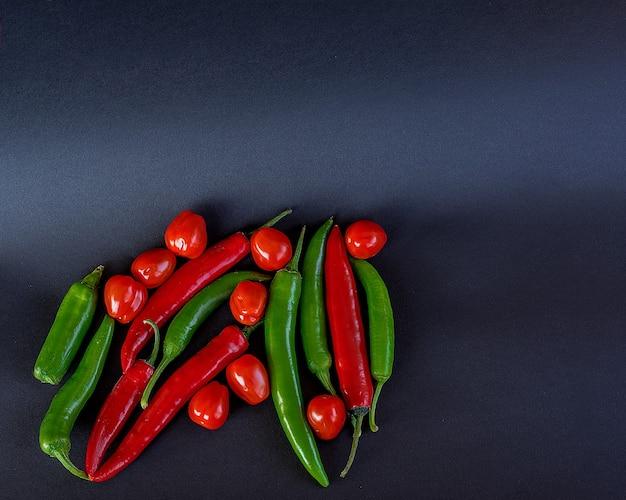 Widok z góry na pomidorki koktajlowe i mini czerwone ostre papryczki chili w starym talerzu na ciemnym drewnianym stole.