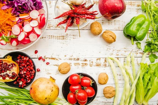 Widok z góry na pomidory czereśniowe; czerwone papryczki chilli; wiosenna cebula; czosnek; sałata; pietruszka; dojrzały granat; czerwonawy i orzech