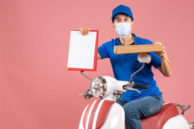 Widok z góry na pracowitego kuriera w masce medycznej w kapeluszu, siedząc na skuterze, trzymając dokument na pastelowym brzoskwiniowym tle