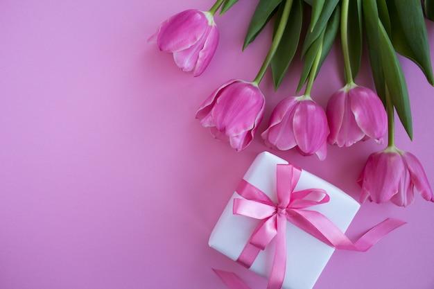 Widok z góry na prezent i różowe tulipany na różowej powierzchni