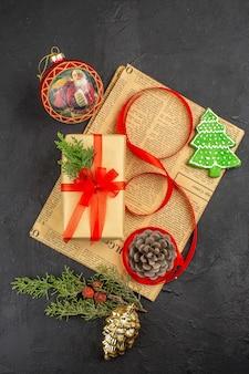 Widok z góry na prezent świąteczny w brązowej wstążce jodłowej gałęzi na gazecie szczegóły bożonarodzeniowe na ciemnej powierzchni