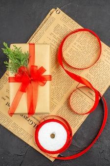 Widok z góry na prezent świąteczny w brązowej wstążce z gałęzi papieru na gazecie na ciemnej powierzchni