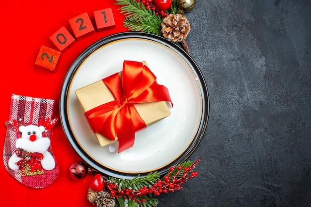 Widok z góry na prezent ze wstążką na talerzu obiadowym akcesoria do dekoracji gałęzie jodły i numery świąteczne skarpety na czerwonej serwetce na czarnym tle