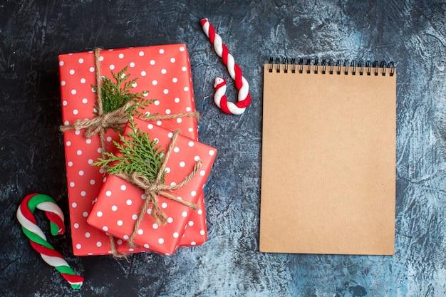 Widok z góry na prezenty świąteczne, cukierki i pusty notatnik
