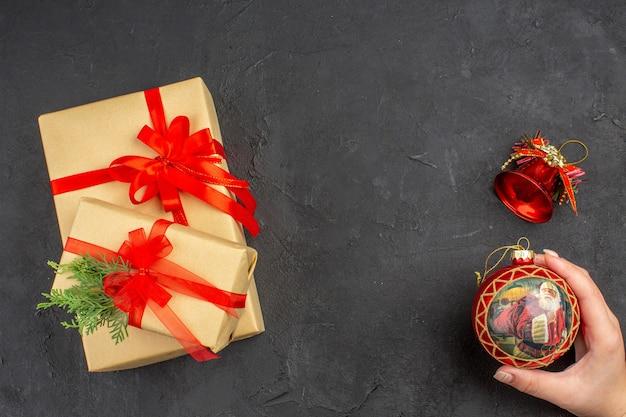 Widok z góry na prezenty świąteczne w brązowym papierze związanym czerwoną wstążką świąteczną zabawką w kobiecej dłoni na ciemnej powierzchni