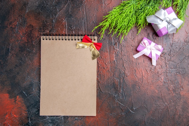 Widok z góry na prezenty świąteczne z różowym pudełkiem i białą wstążką gałęzi drzewa notatnik na ciemnoczerwonej powierzchni