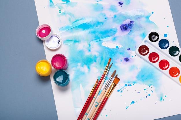 Widok z góry na proces pracy podkładki papierowej z akwarelą, materiałów do malowania akwarelowego i pędzli