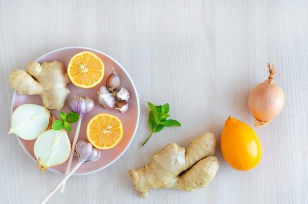Widok z góry na produkty wspomagające układ odpornościowy, cytrynę, imbir, czosnek, cebulę na drewnie