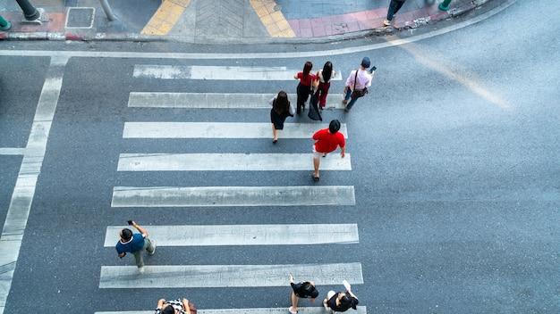 Widok z góry na przejście dla pieszych z ludźmi przechodzącymi przez ulicę z oznakowaniem.