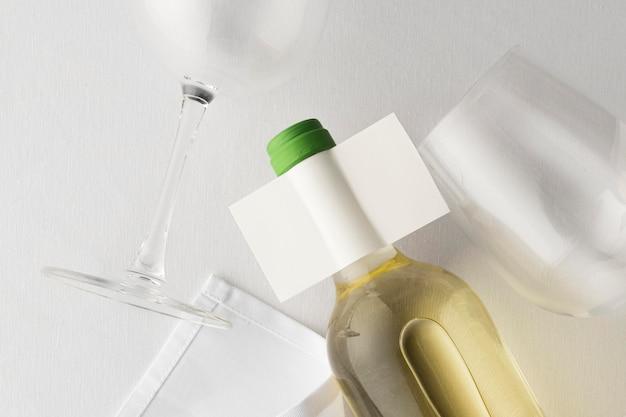 Widok z góry na przezroczystą butelkę wina z pustą etykietą i okularami