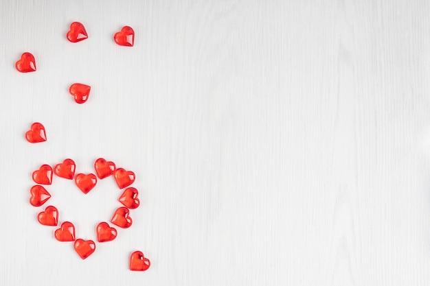Widok z góry na przezroczyste cukierki w kształcie małych czerwonych serc ułożonych na białym tle drewnianych