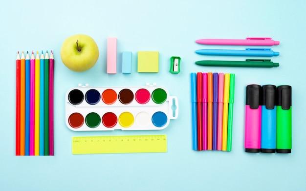 Widok z góry na przybory szkolne z akwarelą i kolorowymi ołówkami