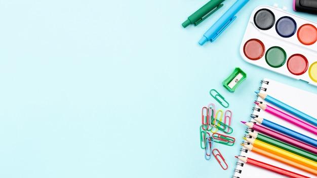 Widok z góry na przybory szkolne z akwarelą i ołówkami