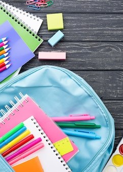 Widok z góry na przybory szkolne z plecakiem i kolorowymi ołówkami