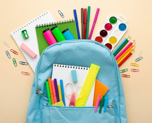 Widok z góry na przybory szkolne z plecakiem i kredkami