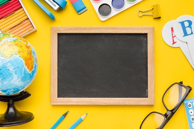 Widok z góry na przybory szkolne z tablicy i okulary