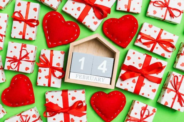 Widok z góry na pudełka, drewniany kalendarz i czerwone tekstylne serca