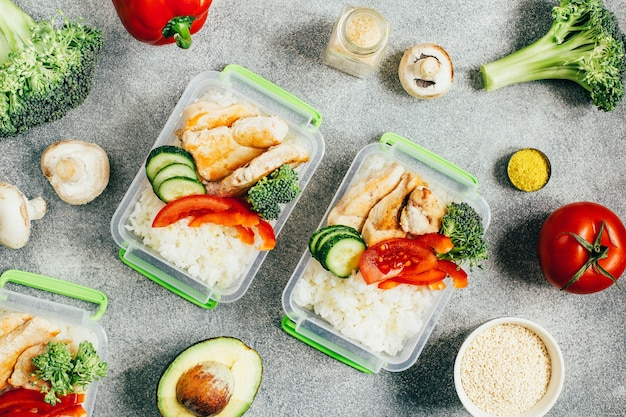 Widok z góry na pudełka na lunch z warzywami, ryżem, mięsem na szarej powierzchni