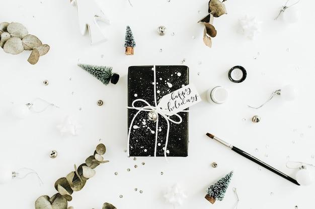 """Widok z góry na pudełka prezentowe z cytatem """"wesołych świąt"""" i dekoracjami na białej powierzchni"""