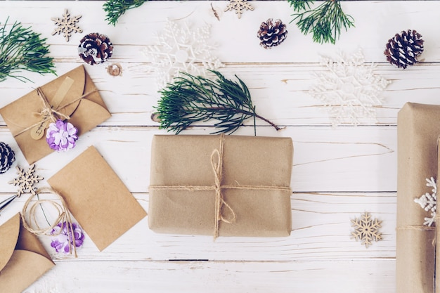 Widok z góry na pudełko i kartki świąteczne na drewnianym stole z dekoracją świąteczną.
