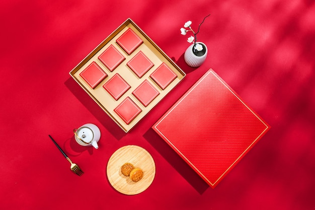Widok z góry na pudełko księżycowych ciastek z czajnikiem, widelcem i wazonem na czerwonej powierzchni