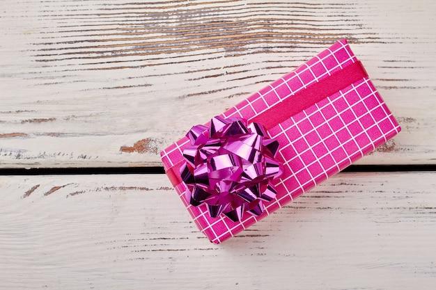 Widok z góry na pudełko prezentowe. różowa kokardka na opakowaniu prezentowym. tradycyjny styl pakowania prezentów.