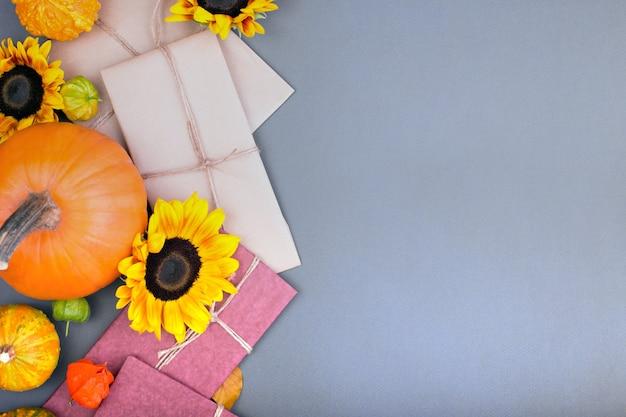 Widok z góry na pudełko upominkowe rzemieślnicze i dynie na szarym tle