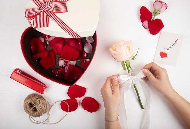 Widok z góry na pudełko w kształcie serca wypełnione czerwonymi płatkami róży lina zszywacza w kolorze czerwonym i kobiece ręce wiążące białą różę wstążką na białym tle