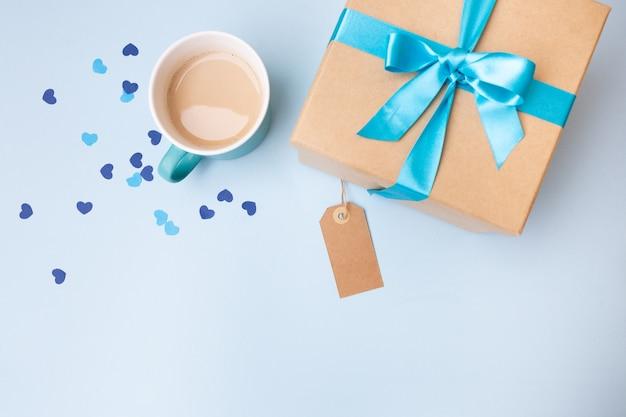 Widok z góry na pudełko z niebieską kokardą, kawę w niebieskim kubku i serduszka konfetti, śniadanie z etykietą kopiowania