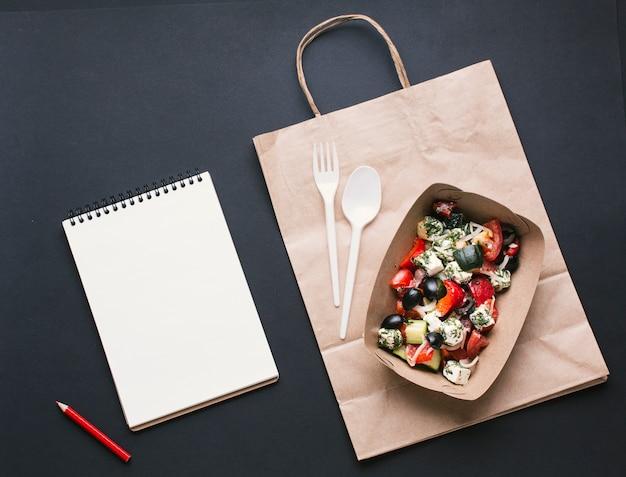 Widok z góry na pudełko z sałatką na papierowej torbie
